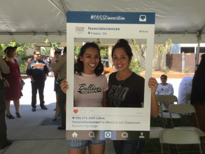 Two female students smile and pose for a picture with the COSS Convocation Instagram frame