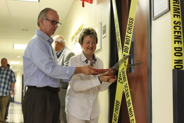 Dr. Peter English and Dr. Candice Skrapec begin cutting the crime scene tape.